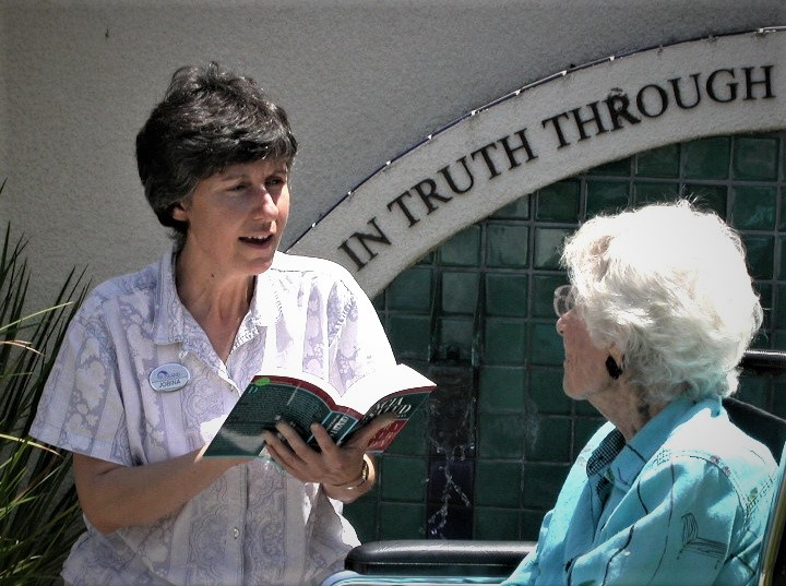 Volunteer reading to patient by outdoor fountain